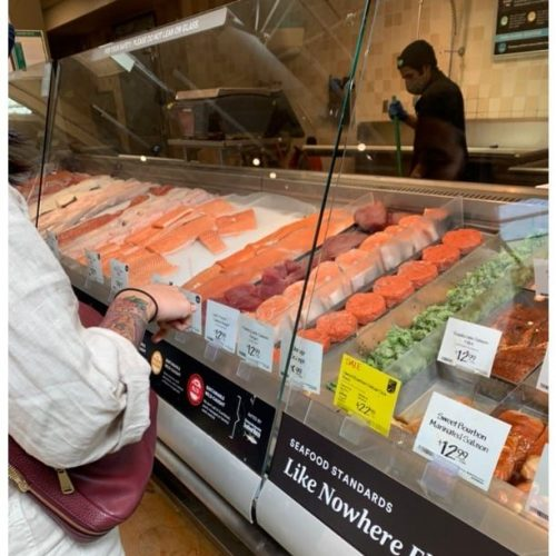 A person standing at a seafood counter choosing what to purchase