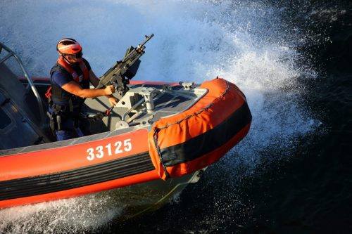 Coast guard with a machine gun enforcing fishery laws